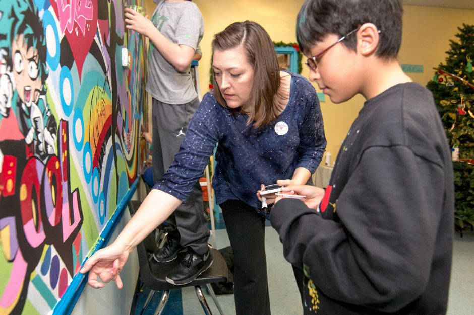 Michele Urban, of Wallingford, helps Vlad Knap, 11, paint a mural being painted at the Ulbrich Boy