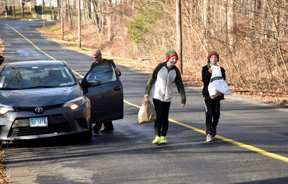 A Durham resident delivers food donations to Joe Bugai (left) and Justin Rowe (right) while they go door-to-door during the 13th annual Community Round-up in Durham and Middlefield on Saturday, Dec. 1, 2018. The event collected more than 13,000 food items and about $3,500 to go to Durham and Middlefield Social Services, and Amazing Grace in Middletown. | Bailey Wright, Record-Journal
