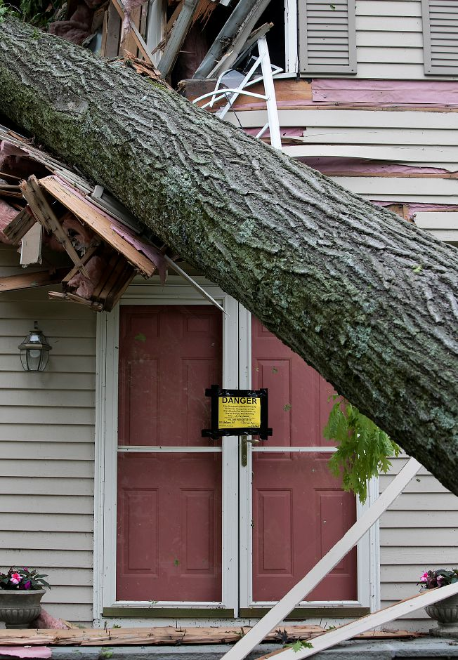 A home at 120 Bellamy Rd. is declared unsafe after a fallen tree heavily damaged the structure during Tuesday