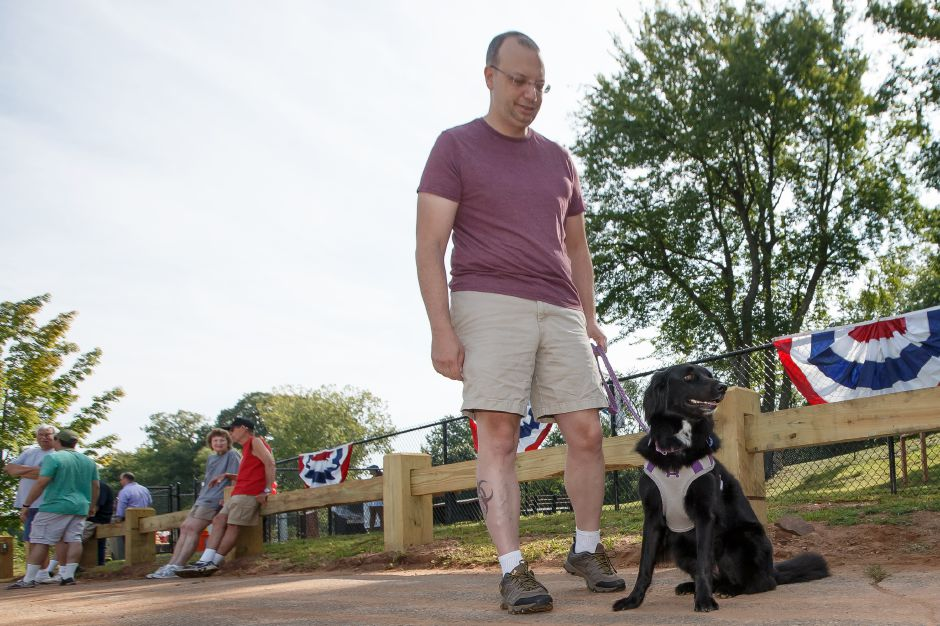 "James Colombo hold ""Molly"" a three year old Flatt Coat Retriever Saturday during the opening of the Meriden Dog park in Meriden August 25, 2018 