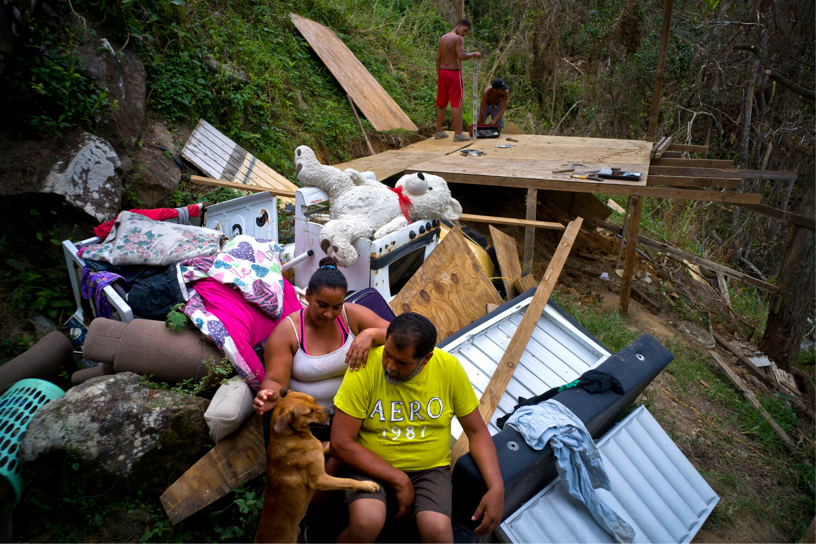 "CORRECTS FROM SAN LAZARO TO SAN LORENZO AND MORAVIS TO MOROVIS - Yadira Sortre and William Fontan Quintero pose to what is left of their belongings, destroyed by Hurricane Maria while their children build a room to protect themselves from the elements, in the San Lorenzo neighborhood of Morovis, Puerto Rico, Saturday, Sept. 30, 2017.  ""We lost everything,"" Fontan said. They have three children, one lives in Chicago and two live with them in Puerto Rico. (AP Photo/Ramon Espinosa)"