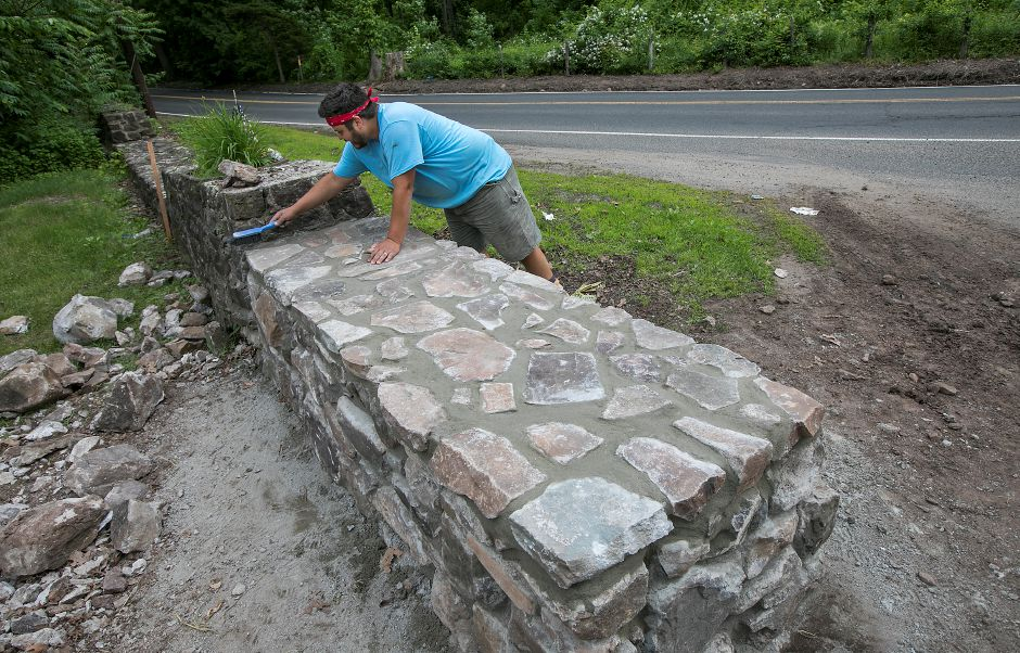 Anthony Perez, a worker for Meriden based home improvement contractor Jack Biafore LLC, cleans up after helping build a new stone wall at the entrance to Giuffrida Park in Meriden, Friday, June 8, 2018. The former wall was damaged by a vehicle last year. Dave Zajac, Record-Journal