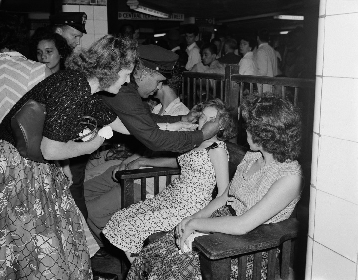 Juana Otero, a victim of heat exhaustion in the abnormally packed Grand Central subway station in New York, gets assistance from transit policeman Arthur Dixon as other victims rest in a corner of the station, July 16, 1956. Numerous other rush hour travelers required aid as a surging mass of humanity sought shuttle transport to the West Side subway system after a busy section of the East Side tube was put out of commission as a result of the weekend fire in the Old Wanamaker department store. (AP Photo/Jacob Harris)