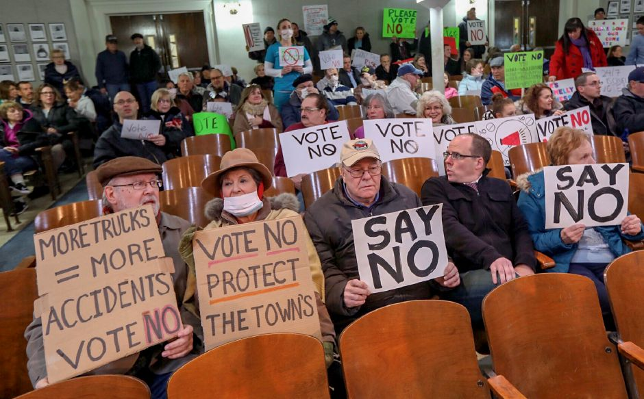 Residents hold signs in the Wallingford Town Council Chambers while protesting development of the former Bristol-Myers Squibb property, Mon. Jan. 14, 2019. Dave Zajac, Record-Journal