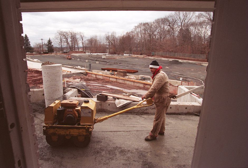 RJ file photo - Carlos Arias of Ansonia compacts the soil in front of the bath house at Community Pool in Wallingford March 1, 1999.