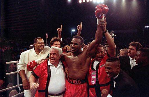 "The new world heavyweight champion Evander Holyfield is supported by his trainers Lou Duva, left, and George Benton, right, after his third round knock-out of James ""Buster"" Douglas, on October 25, 1990, at the Mirage Hotel in Las Vegas, Nevada. (AP Photo/ Douglas C. Pizac)"