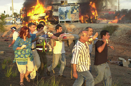 Israelis carry a victim from the site of a bombing in Karkur Junction, northern Israel Monday, Oct. 21, 2002. A car pulled up next to a bus and exploded in northern Israel during Monday afternoon rush hour, killing at least thirteen people and wounding more than 30, as the entire bus was set aflame, background, according to police and radio reports. (AP Photo/Ronen Lidor)