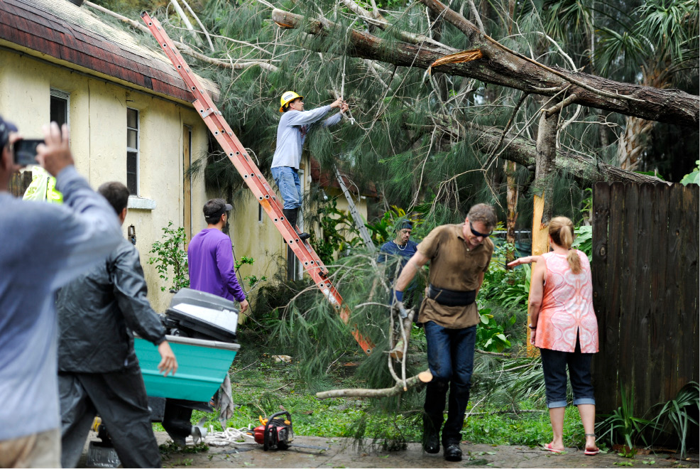 Steve Miccio secures a tree limb with a rope as he and others work to remove the tree from the roof of his Gulf Road home Tarpon Springs, Fla., Monday, Sept. 11, 2017. Miccio and his family were not home at the time when the tree fell. Hurricane Irma brought heavy wind and rain as it passed Tampa Bay. (Chris Urso/Tampa Bay Times via AP)