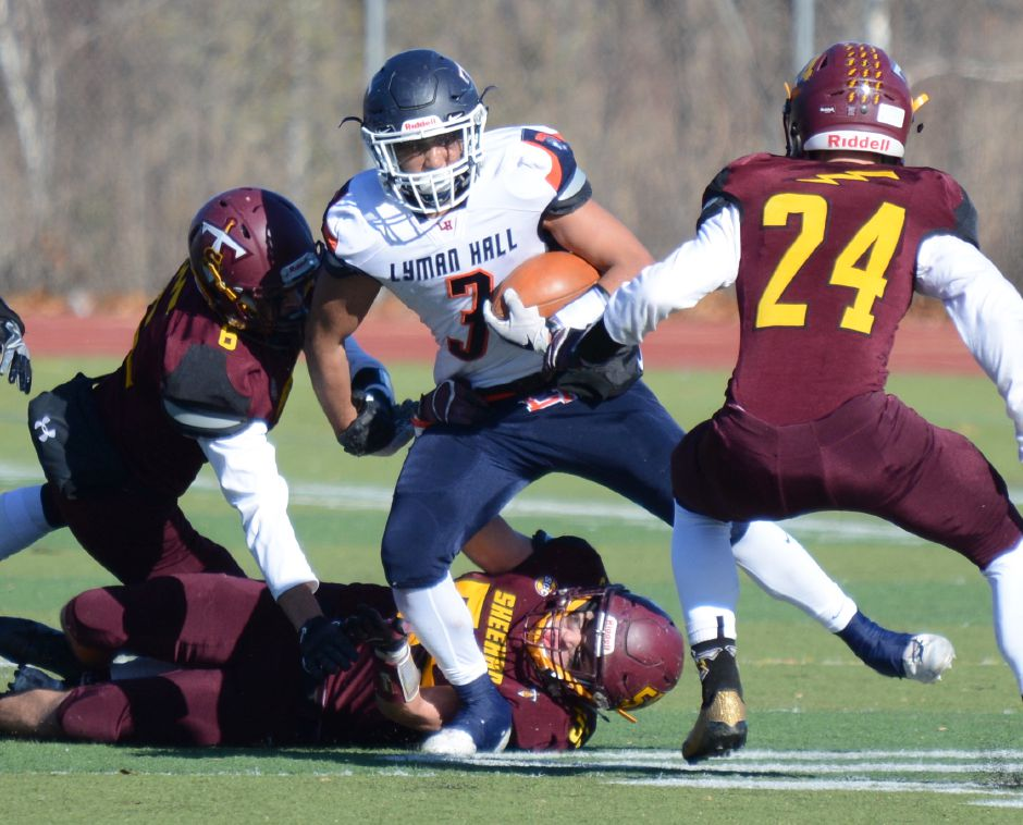 Austin Ruiz, of Lyman Hall, is tackled in the team's annual Thanksgiving Day football game against Sheehan on Thursday, Nov. 23, 2017. The Titans defeated the Trojans, 49-20. | Bryan Lipiner, Record-Journal