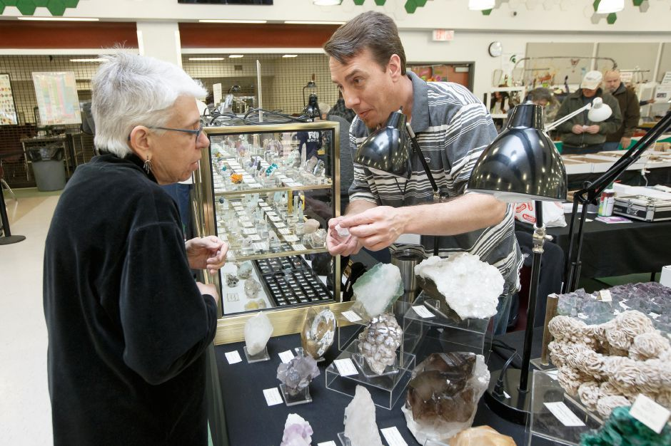 Barbara Liebman of Newtown gets some help from Raymond Hall of Hall of Gems Saturday during the 47th Annual Meriden Gem Show sponsored by the Lapidary & Mineral Society of Central Connecticut at Maloney High School in Meriden March 3, 2018 | Justin Weekes / Special to the Record-Journal
