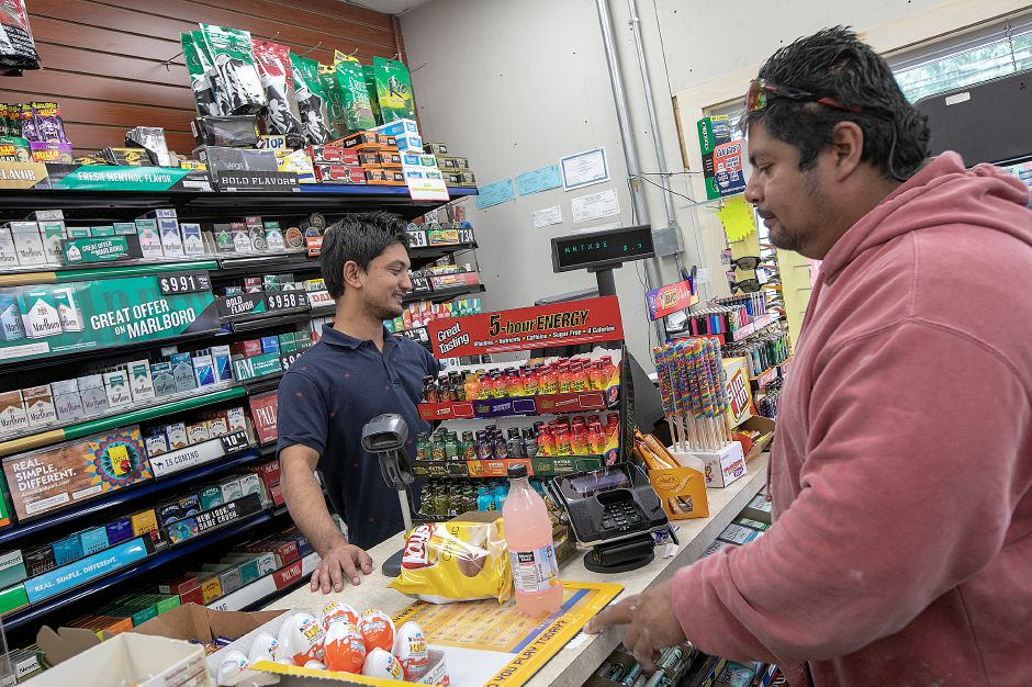 Srijan Katwal, manager of Global Food Mart and gas station, 570 Center St., left, helps customer Erick Martinez, of Wallingford, with a purchase Monday, Sept. 24, 2018. Katwal says his business has been affected by the East Center Street bridge construction site. Kevin Nursick, state Department of Transportation spokesman, said it will be at least two more months before work can recommence, and the project is now expected to last until the summer of 2020. Dave Zajac, Record-Journal