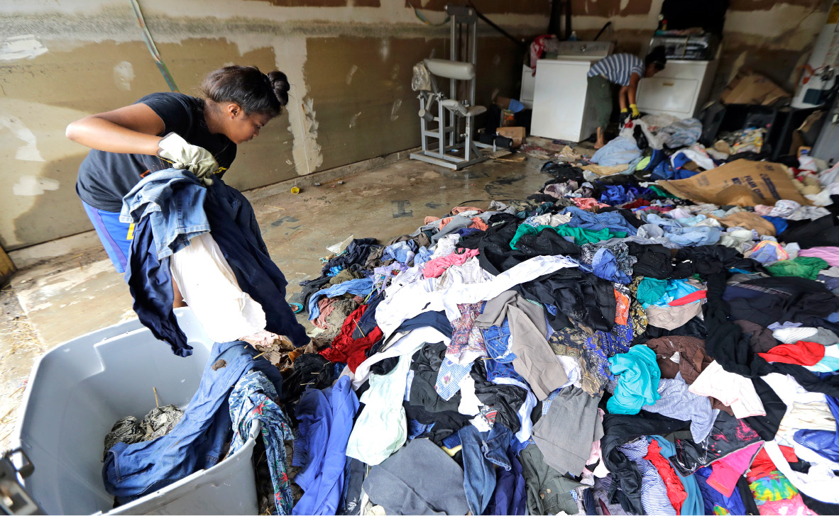 Afhley Lluvia, left, and her mother, Julia, remove clothing from their home on Monday which was destroyed by floodwaters in the aftermath of Hurricane Harvey in Houston. | Associated Press