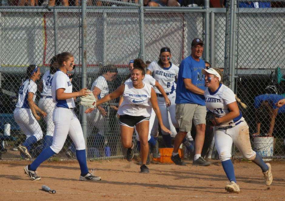 Southington freshman Samantha Sullivan, left, gets swarmed by her teammates after throwing the final pitch of the Class LL championship game Saturday in Stratford. Spencer Davis, Record Journal