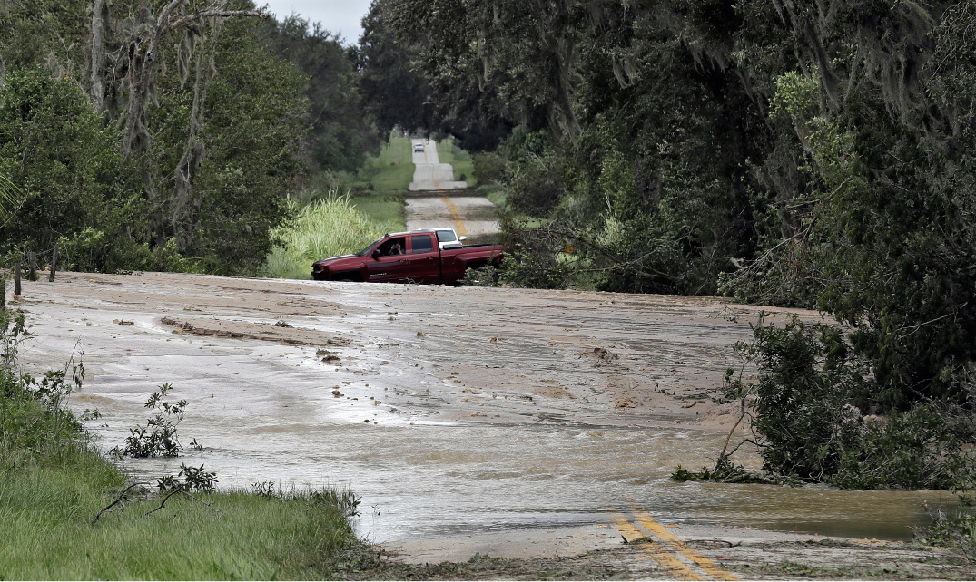 Motorists turn around after a levee from a phosphate plant ruptured from rain and wind associated with Hurricane Irma on Monday, Sept. 11, 2017, in Homeland, Fla. (AP Photo/Chris O