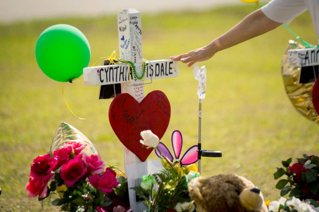 A woman gestures toward a cross honoring Santa Fe High School substitute teacher Cynthia Tisdale Tuesday, May 22, 2018, who was killed during a shooting at the school on Friday, in Santa Fe, Texas. (Marie D. De Jesus/Houston Chronicle via AP)