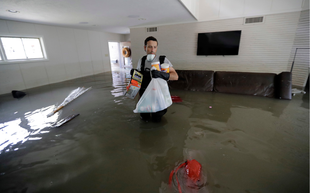 Gaston Kirby walks through floodwater inside his home in the aftermath of Hurricane Harvey, Monday, Sept. 4, 2017, near the Addicks and Barker Reservoirs, in Houston. (AP Photo/David J. Phillip)