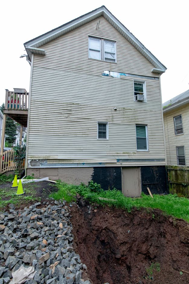 A sinkhole has opened in the backyard of a home at 170 Liberty Street in Meriden. When it appeared early Sunday morning it caused a tree to fall on the home and a vehicle in the parking lot, damaging both. | Devin Leith-Yessian/Record-Journal