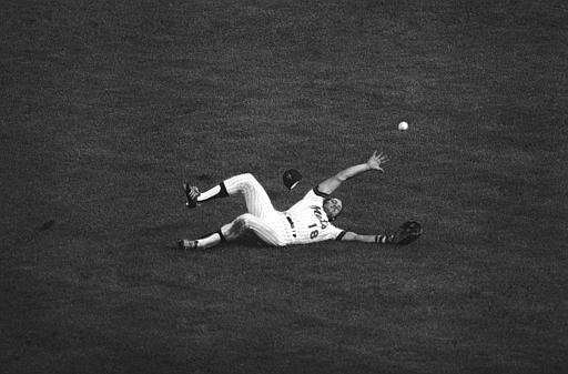 Joel Youngblood of the New York Mets tries to grab a fly ball off the bat of San Francisco Giants Rob Andrews after it fell when Youngblood slipped during their game, Aug. 22, 1978, at New York