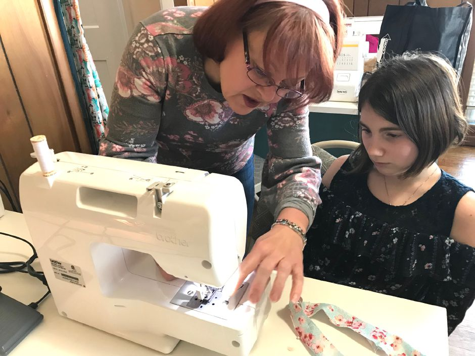Charlotte Stowe helps fifth grader Peyton Bertrand with the sewing machine at Charlotte
