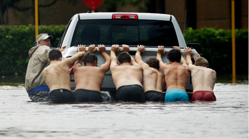 FILE - In this Sunday, Aug. 27, 2017 file photo, a group of people push a stalled pickup through a flooded street in Houston, after Tropical Storm Harvey dumped heavy rains. The remnants of Harvey sent devastating floods pouring into Houston on Sunday as rising water chased thousands of people to rooftops or higher ground. (AP Photo/Charlie Riedel)