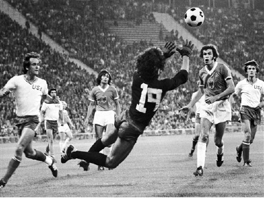 German goalkeeper Bradler reaches out for the ball in front of US attacker Michael Seerey, left, in an Olympic Games soccer tournament match in Munich on Sept. 1, 1972. The German team defeated the Americans 7-0. West German player Baltes is on the right in the dark jersey. (AP Photo)