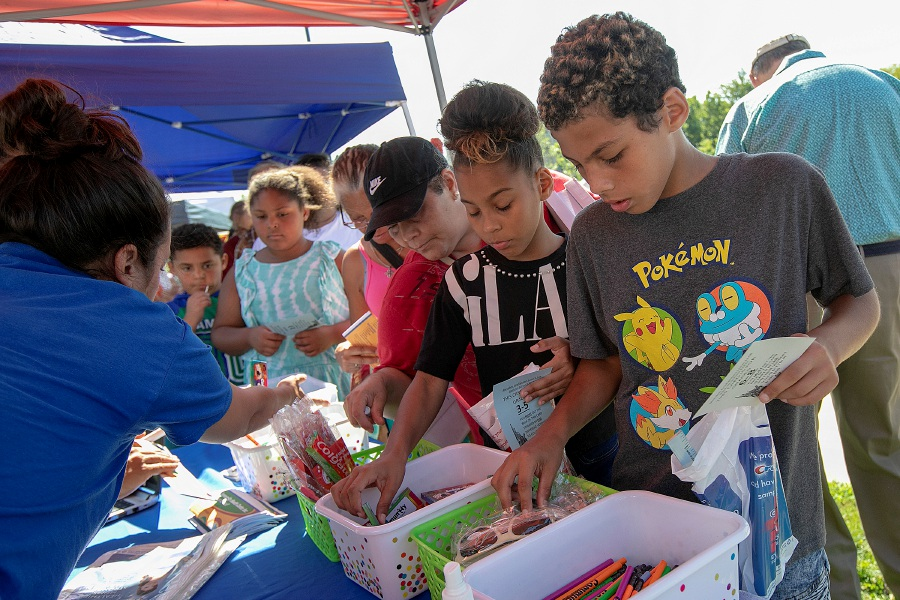 Carlos Rivera, 11, and sister Lileishka, 11, of Meriden, pick up school supplies and other items from the Community Healthcare Center tent during the Meriden Fire Local 1148 annual Back-to-School Expo on the Meriden Green, Tues. Aug. 20, 2019. Dave Zajac, Record-Journal