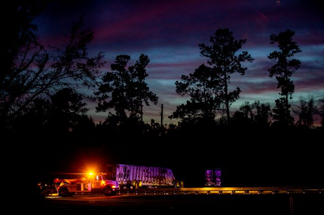 The sun sets over burned semi-trucks and vehicle debris after a wreck with multiple fatalities on Interstate 75, south of Alachua, near Gainesville, Fa., Thursday, Jan. 3, 2019. Two big rigs and two passenger vehicles collided and spilled diesel fuel across the Florida highway Thursday, sparking a massive fire that killed several people, authorities said. (Lauren Bacho/Star-Banner via AP)
