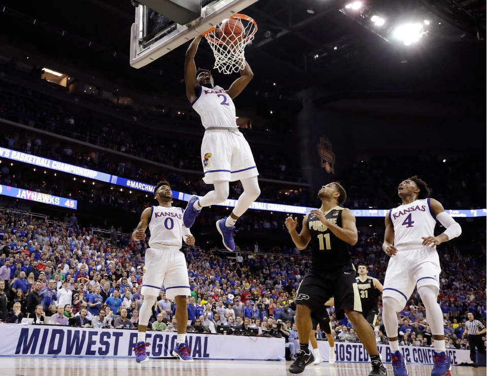 Kansas guard Lagerald Vick (2) dunks over Purdue guard P.J. Thompson (11) during the first half of a regional semifinal of the NCAA men