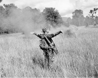 A U.S. Special Forces adviser directs a helicopter to a landing zone in a jungle clearing marked by a smoke grenade, Aug. 22, 1964. (AP Photo/Horst Faas)