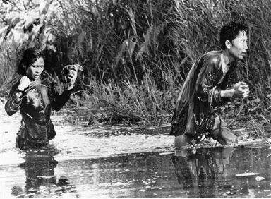 A peasant and his wife wade out of a swampy thicket after South Vietnamese rangers had raked it with grenades and automatic weapons fire in Vietnam, August 31, 1966. The rangers had assaulted their hamlet in a Dien district some 140 miles southwest of Saigon in search of Viet Cong, forcing the residents into hiding. The peasant told the rangers that about 1,000 Viet Cong had been in the area earlier. He was arrested and taken along by the rangers, who left his wife behind after questioning. (AP Photo)