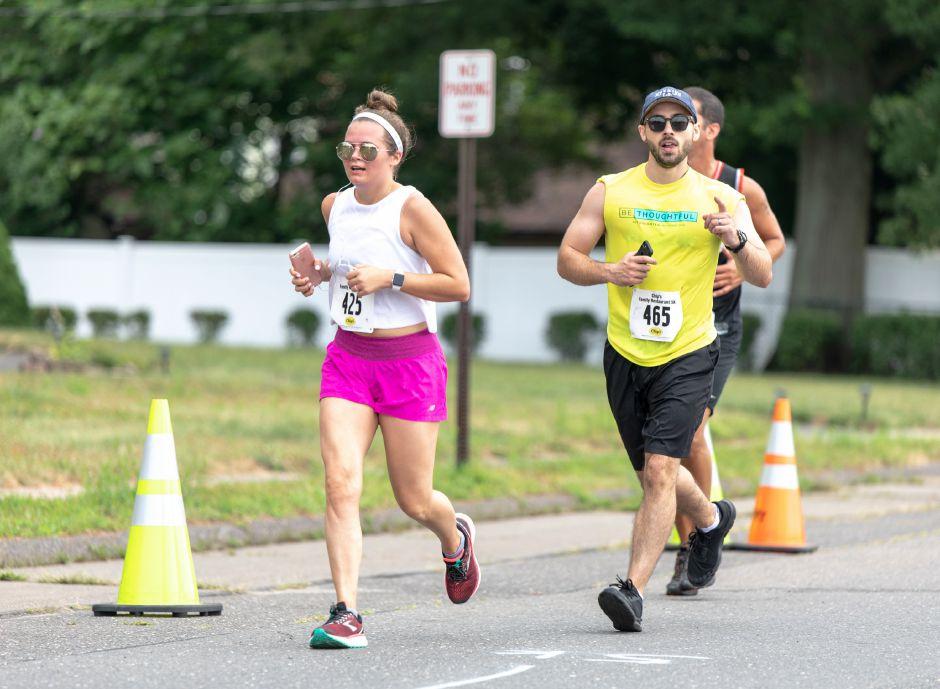 Jamie Wetmore and Robert Lee run down Locust Street during the Chips Family Restaurant Road Race on July 21, 2019. The run started on East Street in front of Plainville High School and ended on Robert Holcomb Way. | Devin Leith-Yessian/Plainville Citizen