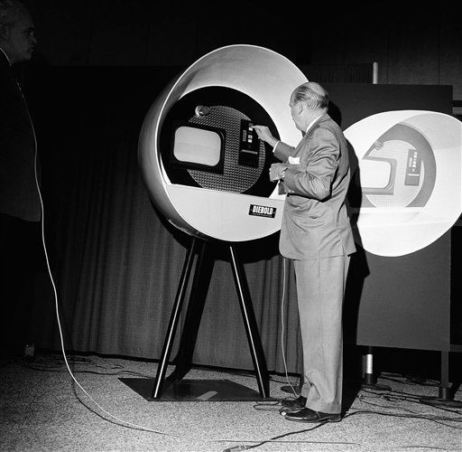 "This new ""banking"" machine was displayed for the first time at the American Bankers Association annual meeting in San Francisco, Calif., Oct. 25, 1966. Banks of the future may have ""tellers"" installed in office and apartment house lobbies. Richard Glyer demonstrates how to deposit a check in one. Through the medium of automation he can talk to a teller whom he sees on the television screen. She will answer his questions, cash checks and issue currency from his account. (AP Photo/Ernest K. Bennett)"
