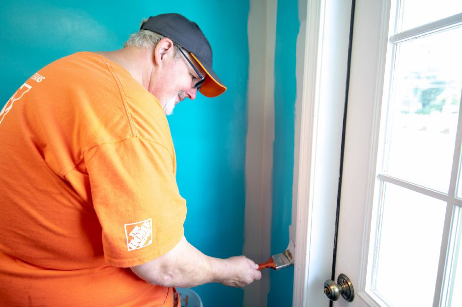 Bill Kiely, Team Depot Community Captain, repaints the walls of one of the buildings at Lisa Inc