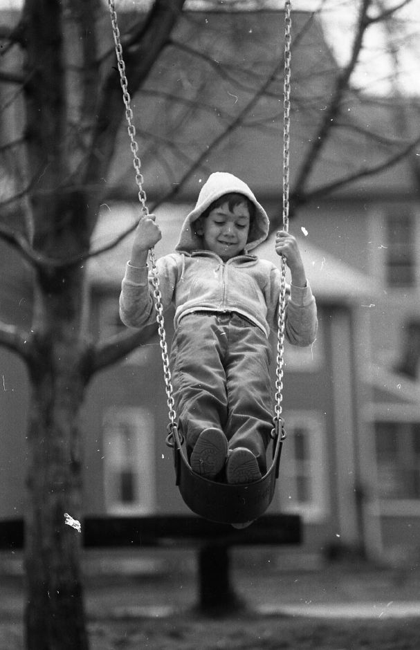RJ file photo - Frank Levigne, 8, gazes at the ground while swinging on a piece of playground equipment at Dutton Park, April 1989.
