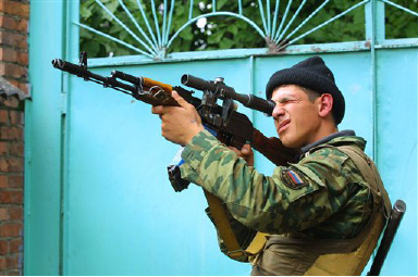 A Russian soldier uses optics as he looks at the seized school in Beslan, Northern Ossetia, Thursday, Sept. 2, 2004. Heavily armed militants, many strapped with explosives, held more than 350 hostages including children for a second day Thursday inside a provincial Russian school as negotiators scrambled to find a way out of the tense stand-off. (AP Photo/ Musa Sadulayev)