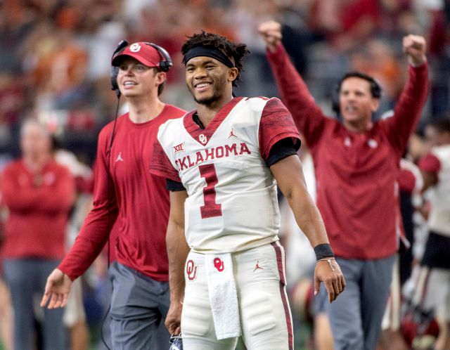 FILE - In this Dec. 1, 2018, file photo, Oklahoma quarterback Kyler Murray (1) celebrates on the sidelines after throwing a touchdown against Oklahoma during the second half of the Big 12 Conference championship NCAA college football game, in Arlington, Texas. A record number of college football players are bypassing remaining years of eligibility to enter the NFL draft, including Heisman Trophy winner Kyler Murray. (AP Photo/Jeffrey McWhorter, File)