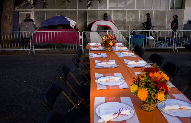 Homeless tents are pitched on a sidewalk in the Skid Row area of downtown Los Angeles Wednesday, Nov. 22, 2017, as tables are set up on the street to serve dinner to homeless people at the Los Angeles Mission