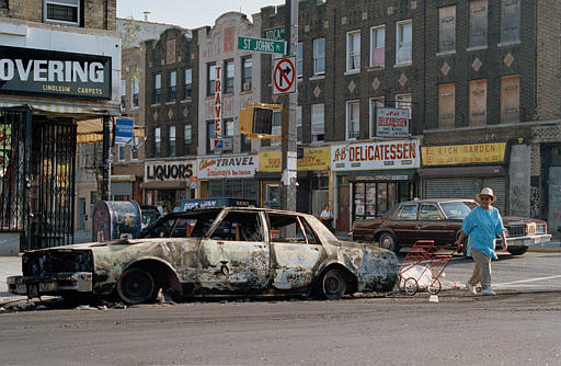 A woman passes a fire-bombed car as she crosses St. Johns Place on Utica Avenue in the Crown Heights sectioin of Brooklyn, Aug. 22, 1991, after a third night of violence in reaction to the death of a black child who was killed by a car driven by a Hasidic man.  (AP Photo/David Cantor)