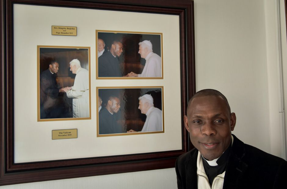 Rev. Kingsley Ihejirika poses in front of pictures hung in his office at Most Holy Trinity Church in Wallingford of him meeting Pope Benedict XVI at the Vatican in November 2010. Ihejirika is raising money to build a medical clinic in his hometown of Obike, Nigeria.| Matthew Zabierek, Record-Journal