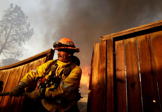 A Los Angeles County firefighter pulls a hose to protect a house during wildfire in the Lake View Terrace area of Los Angeles, Tuesday, Dec. 5, 2017. (AP Photo/Chris Carlson)