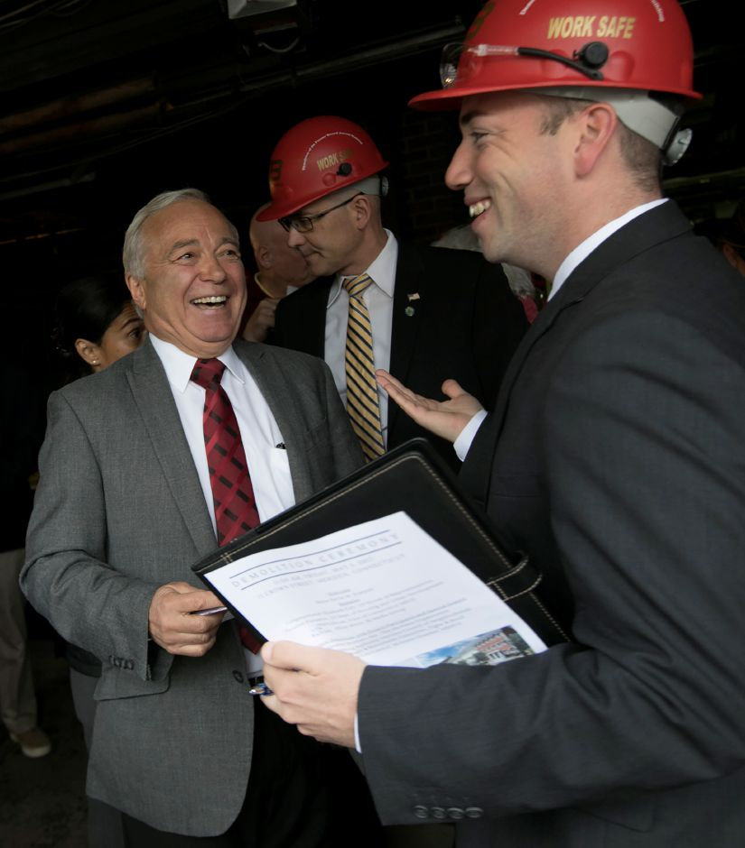 Eliot White, fourth generation president and publisher of the Record-Journal, left, and Mayor Kevin Scarpati, right, share smiles before thr start of a demolition ceremony at the publication