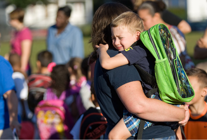 Zachary Crispino, 4, of Meriden, clings to his mother, Karri, prior to the start of the first day of extended-day school at Roger Sherman in Meriden on Wednesday. Students now attend the school for an additional 100 minutes per day, using the extra time for more hands-on enrichment activities.| Dave Zajac / Record-Journal