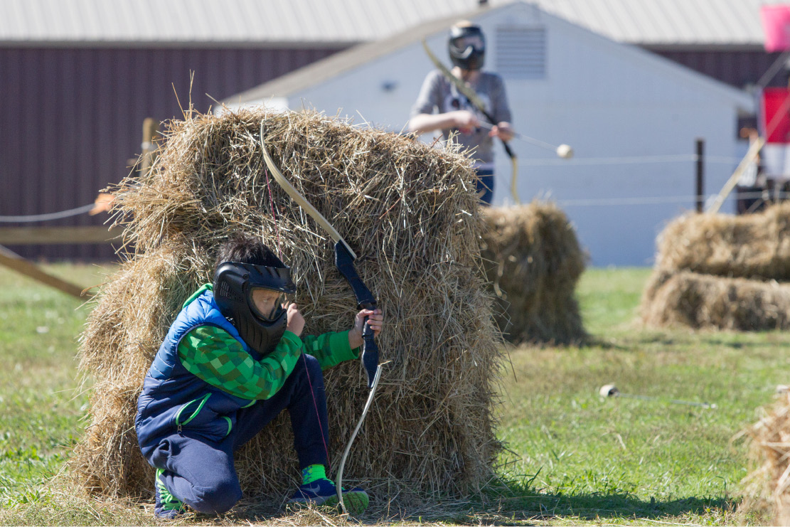 Aidan Treacy 9 of Trumbull crouches behind a hay bail during an archery game Monday during the Connecticut Renaissance Faire at the North Haven Fair Grounds. | Justin Weekes /  Special to The Sun