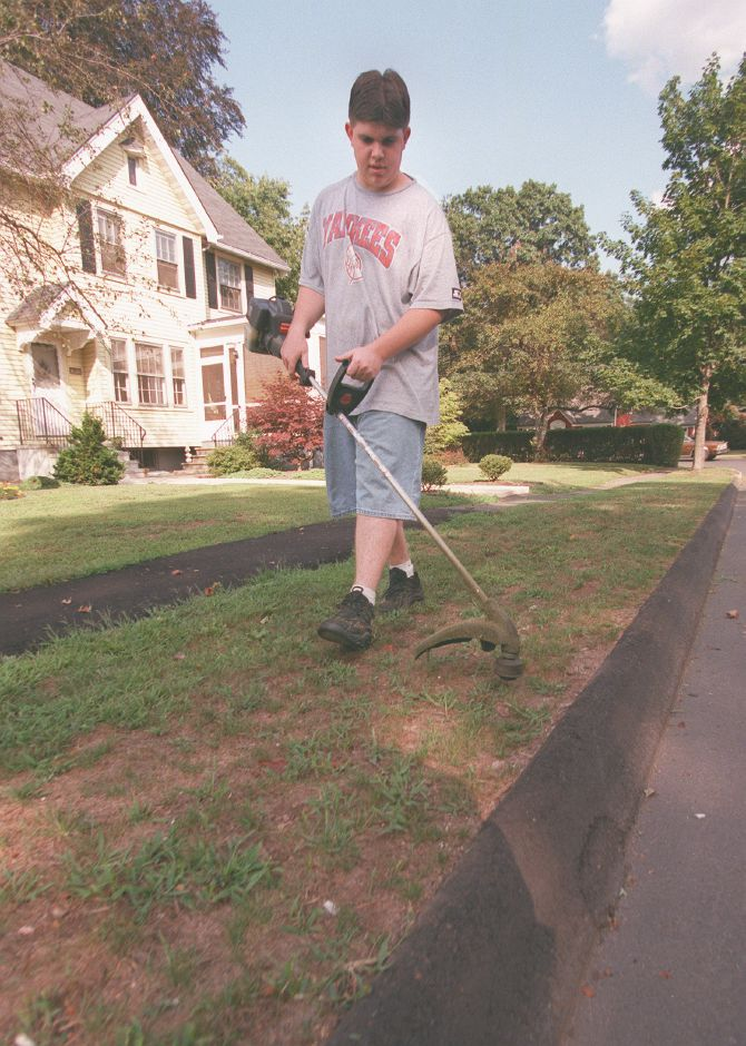 RJ file photo - Chris Eckels, 14, trims the grass in front of his grandmother