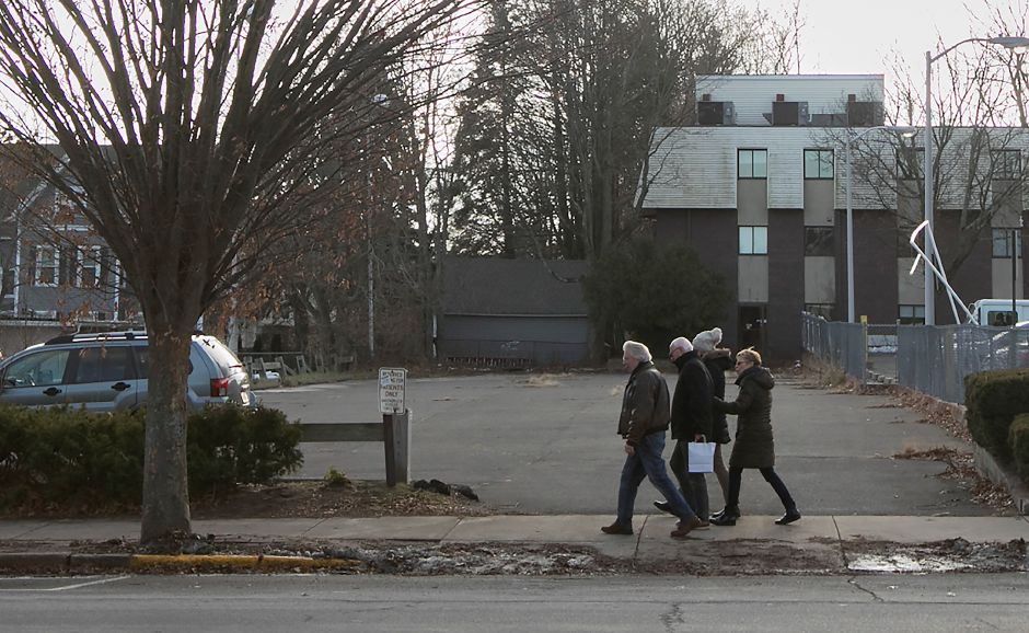 A group walks past a lot on Center Street next to the Wallingford Post Office, Tuesday, Dec. 19, 2017. A rooftop cafe has been proposed for the lot. Dave Zajac, Record-Journal