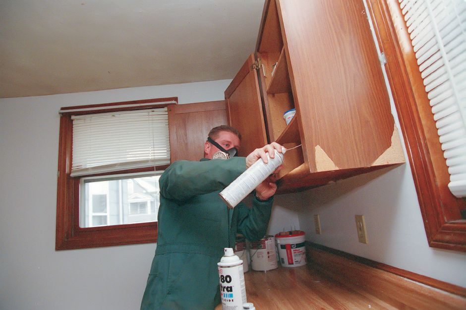RJ file photo - Arnold Camire of Meriden applies some crack and crevice insecticide treament to the inside of a cupboard in a house on First Street in Meriden, Jan. 1999. Camire, an exterminator for 15 years, has been in business for himself for the past six years.