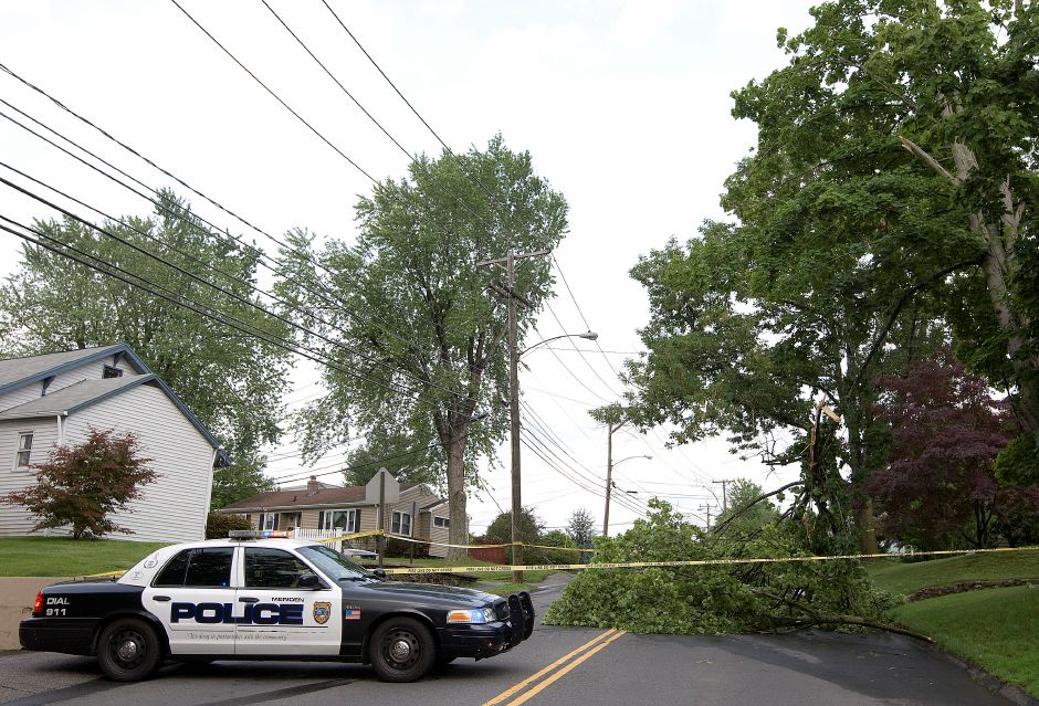 Meriden police block off a portion of Hall Ave. in Meriden after a tree limb came down over wires and the road Tuesday afternoon, June 23, 2015. | Dave Zajac/Record-Journal