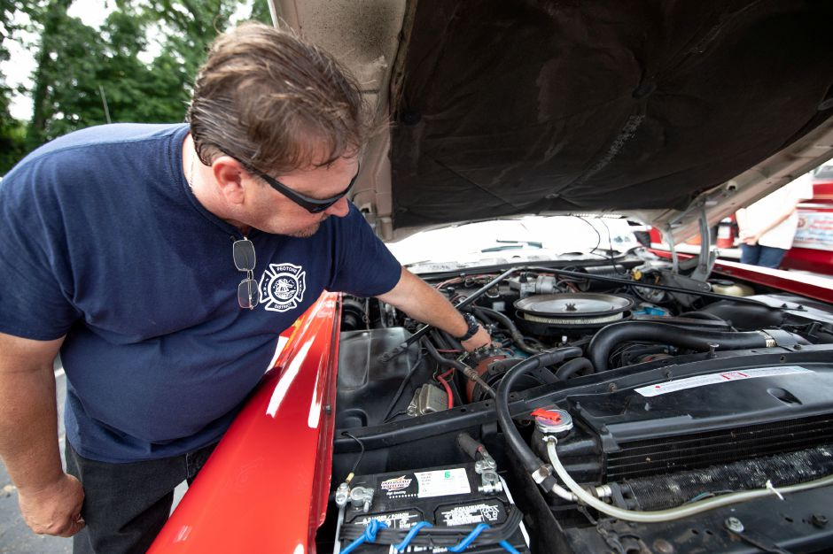 Brian Sullivan, of Wallingford, checks the engine of his restored ambulance at the Wallingford Fire Department