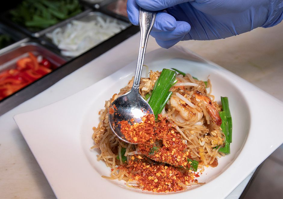Chef Nattapong Chien adds crushed red pepper flakes to a pad Thai shrimp dish at Roodle Rice & Noodle Bar, 1263 S. Broad St., Wallingford, Fri., Aug. 2, 2019. Dave Zajac, Record-Journal