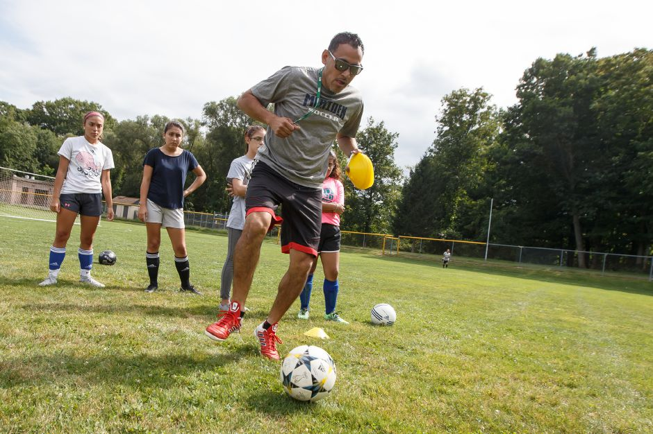 New Platt girls soccer coach Danny Gutierrez demonstrates a dribbling technique during Friday's practice at Platt High School. Gutierrez, who has coached 12 years in the Meriden Soccer Club and last year at Lincoln Middle School, inherits a Platt squad that has gone a combined 12-65-3 in the previous five seasons. | Justin Weekes / Special to the Record-Journal